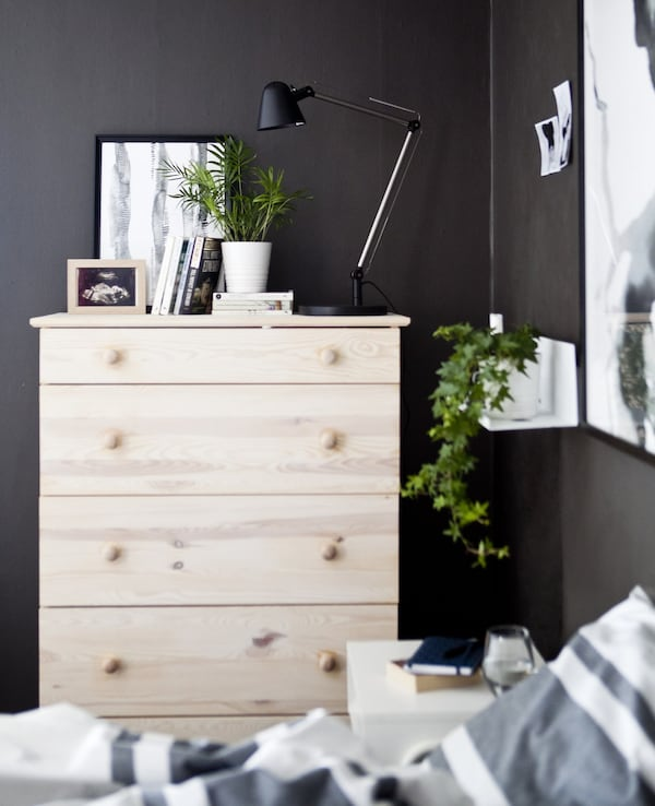 A pale-wood chest of drawers in a dark grey bedroom.