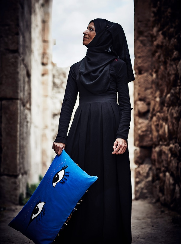 A Palestinian refugee woman artisan is holding a blue cushion with big eyes on it that she made for an IKEA collection.
