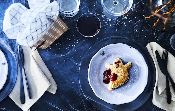 A pankcake shaped like a ghost with jam to resemble blood sitting on a blue plate surrounded by tableware and a wrapped gift.