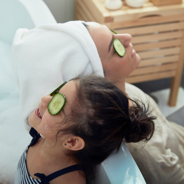 A parent and child leaning against a bath tub with cucumbers on their eyes relaxing.