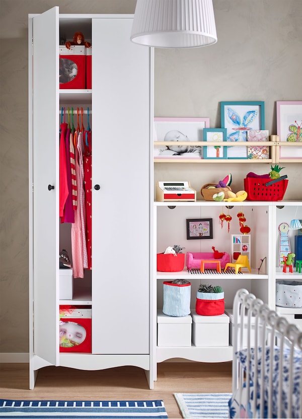 A partially opened IKEA SOLGUL white children's wardrobe, revealing clothes and storage boxes, beside open storage with toys.