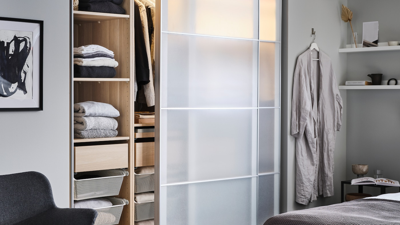 A partly open PAX/SVARTISDAL wardrobe with shelves, drawers and hanging clothes stands in a bedroom near a bed.