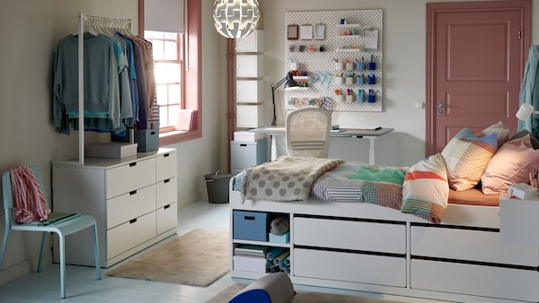 A pastel student room featuring a bed with integrated storage along with a desk and hanging clothes storage nearby.