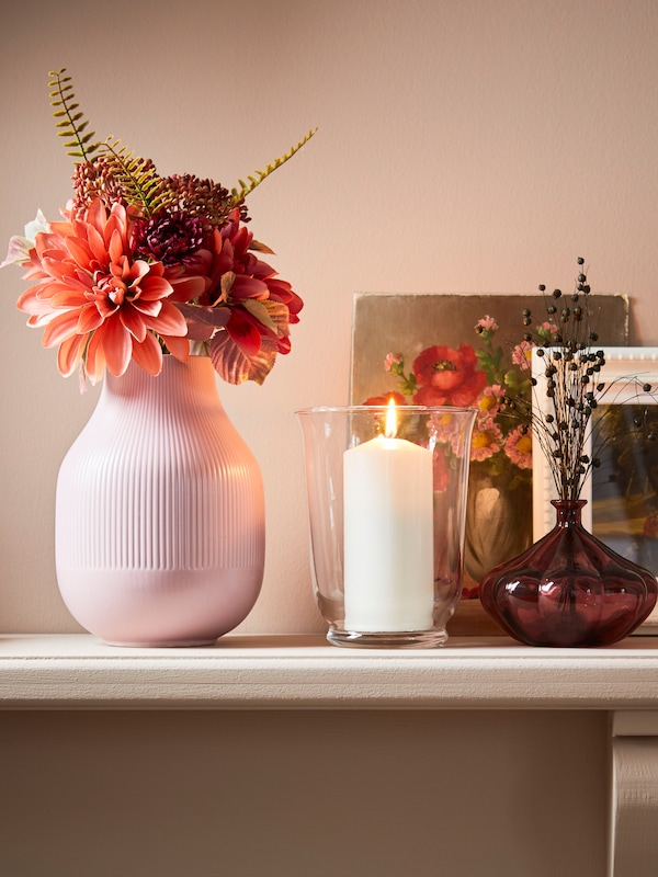 A pastle pink vase sits on a shelf, with a lit candle in a glass vase. A picture frame can be seen also.