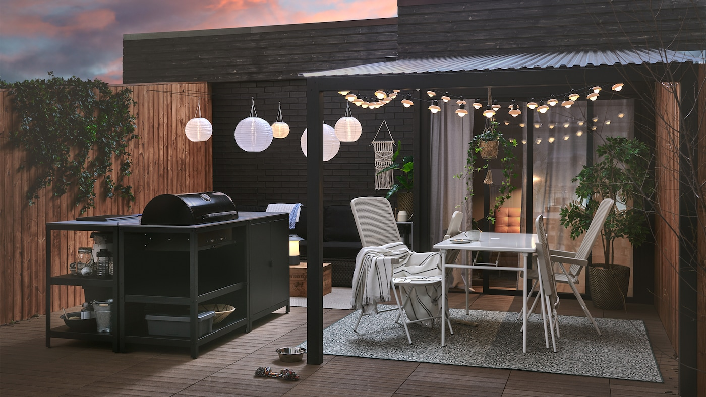 A patio set up for spring with a GRILLSKÄR charcoal grill and kitchen island, TORPARÖ table and chairs, and lights.