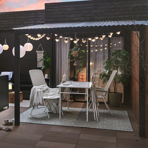 A patio set up with a GRILLSKÄR charcoal grill and kitchen island, TORPARÖ table and chairs, and lights.