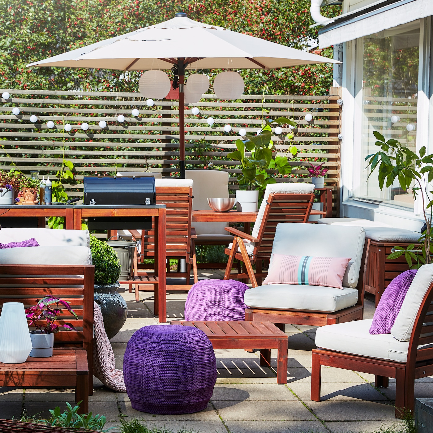 A patio with a barbecue, a 4-seat conversation set in acacia, a beige parasol, purple pouffes and beige outdoor cushions.