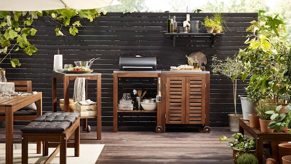 A patio with an outdoor kitchen consisting of a trolley with a charcoal barbecue and a storage cabinet, all in brown stained solid acacia.