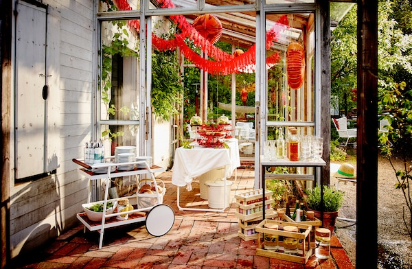 A patio with crayfish decorations hanging from the ceiling and a table laid with serving stands filled with crayfish.