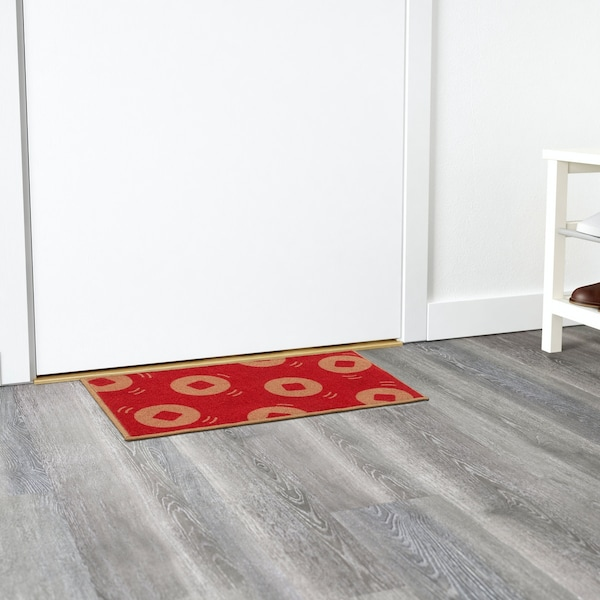 A patterened red and gold SOLGLIMTAR door mat in front of a door.
