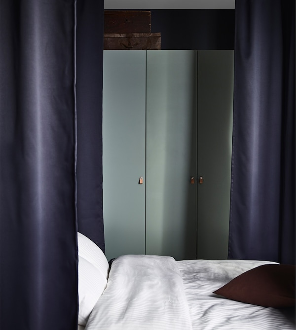 A PAX wardrobe with hinged grey-green doors in a bedroom with dark curtains around the bed.