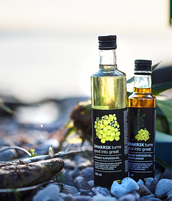 A pebbly beach in the sunset with some grilled fish and two bottles of golden yellow IKEA SMAKRIK rapeseed oil.