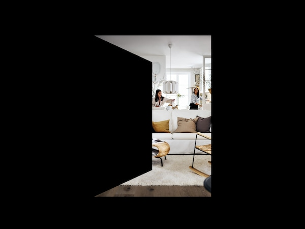 A peek through a graphic of an open door, into an inviting living room in neutral colours, where two women are decorating.