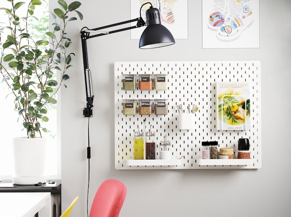 A pegboard mounted on a wall next to a dining table. The pegboard has accessories that store oils, seasonings and a cookbook.