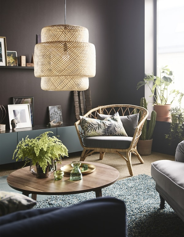 A pendant lamp made of natural woven fibres hangs above a round coffee table in a modern styled living room.