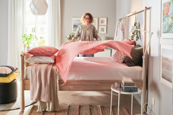 A person covers the bed with a blanket