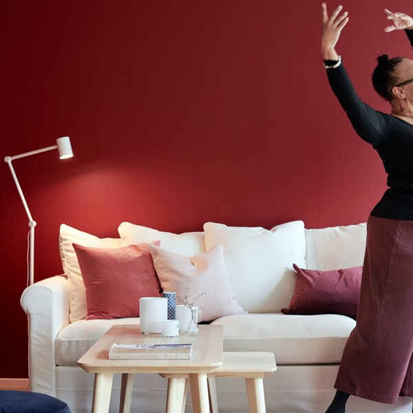 A person dancing slighly out of frame in a red room with a white couch.