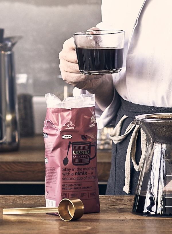 A person holding a cup of coffee made with PÅTÅR special edition coffee and a glass coffee maker for drip coffee.