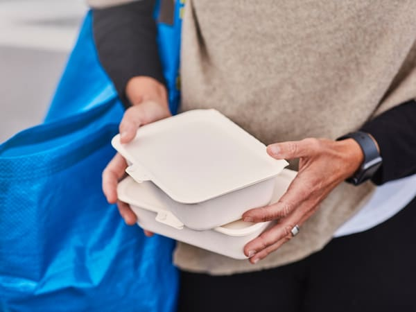 A person holding takeout boxes with an IKEA bag on their shoulder.