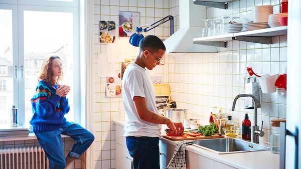 A person in a kitchen, standing by the sink cutting vegetables whilst another person leans against the windowsill whilst holding a tea cup.