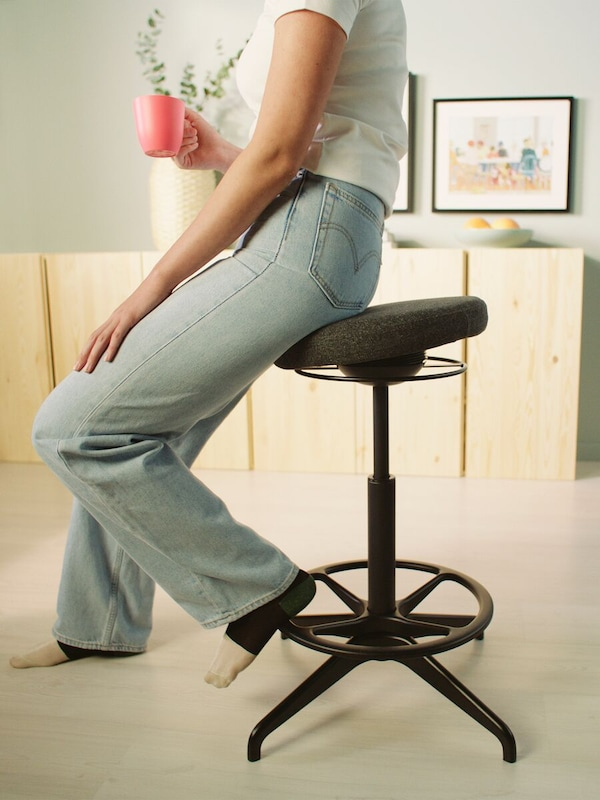 A person in blue jeans and white T-shirt resting on a LIDKULLEN active sit/stand support.