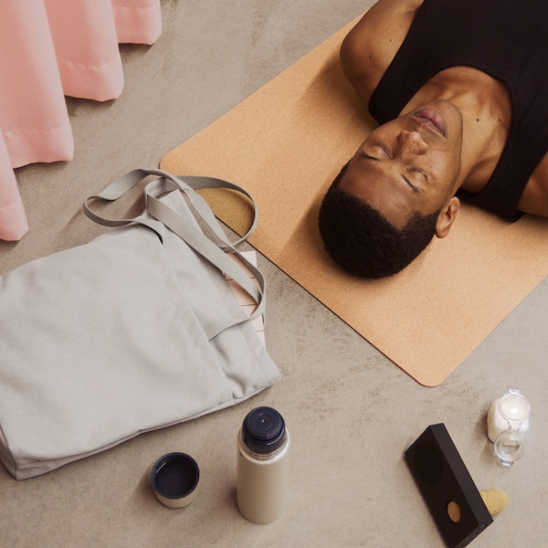 A person laying on a yoga mat with their eyes closed.