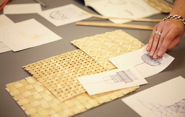 A person laying samples of woven bamboo and sketches out on a table.