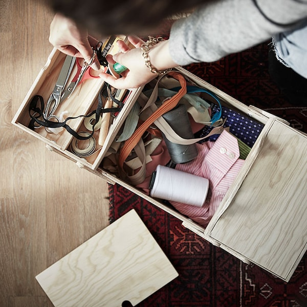 A person leans over a wooden box filled with thread, ribbons, and other crafting necessities.