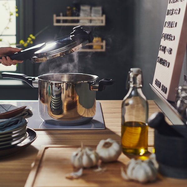 A person lifts the lid off a stainless steel IKEA 365+ pressure cooker on a hob, beside a bamboo APTITLIG chopping board.