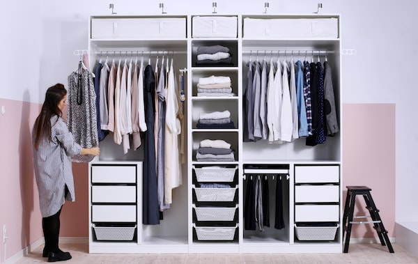 A person places a shirt to hang at the side of a large white wardrobe with rails, drawers, shelves and no doors.