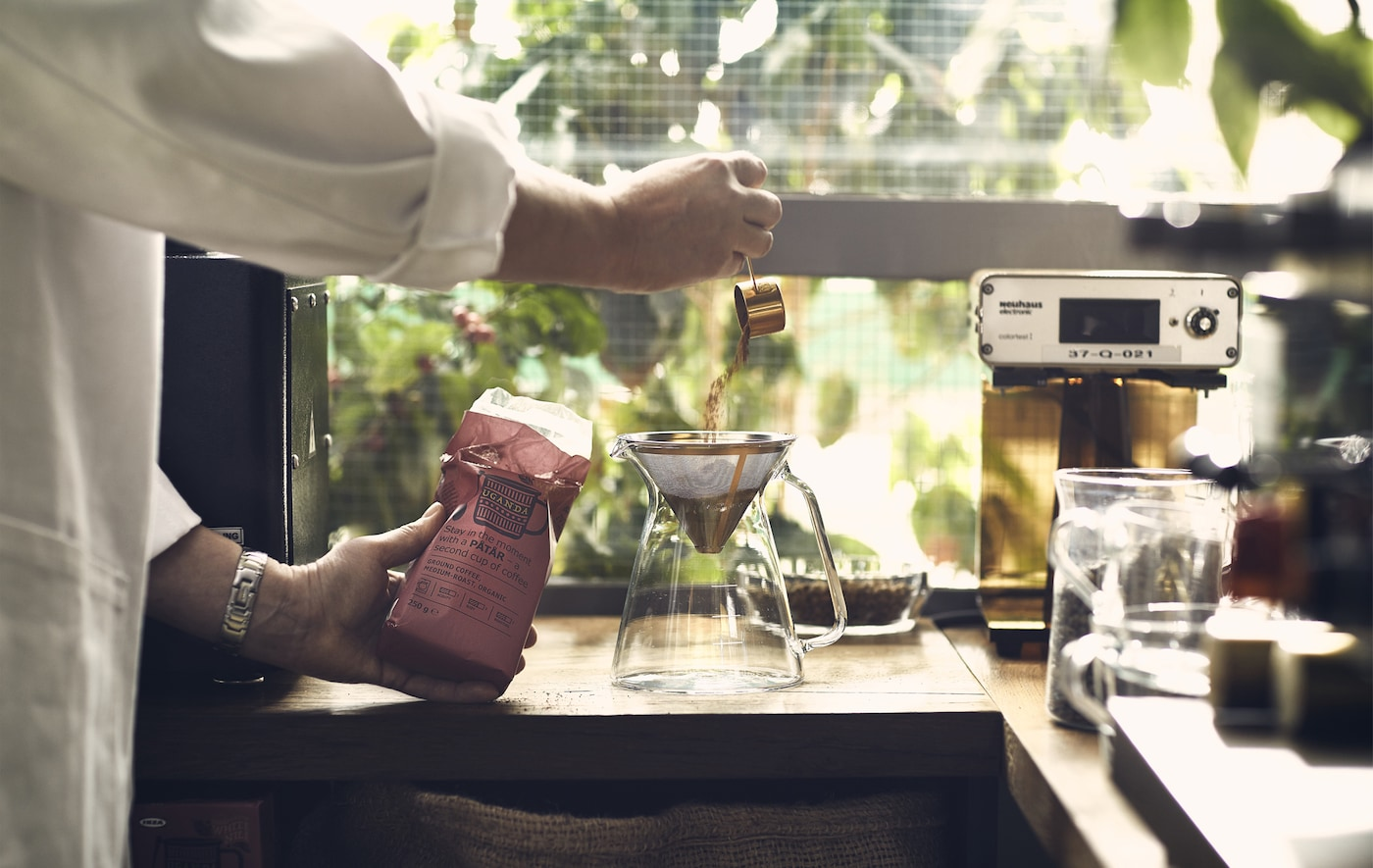 A person pours ground coffee into a filter on a wooden worktop with greenery outside the window behind.