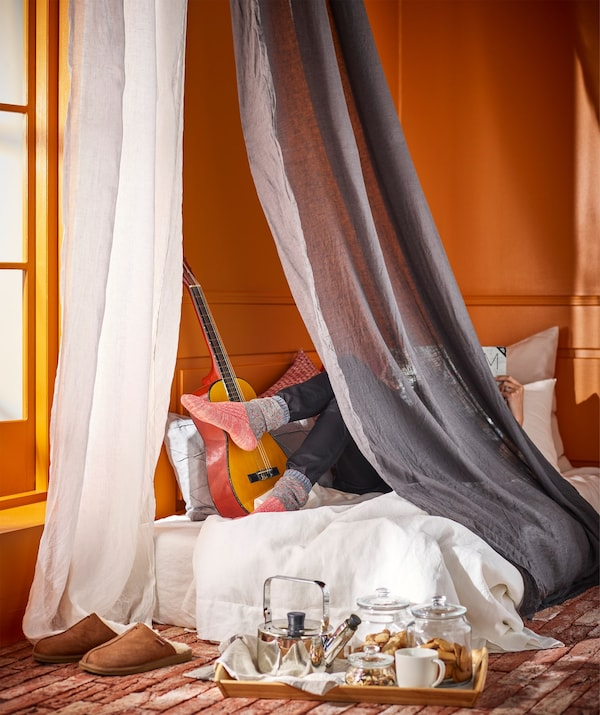 A person relaxing on a spare mattress in the corner of a room behind a canopy of floor length curtains.