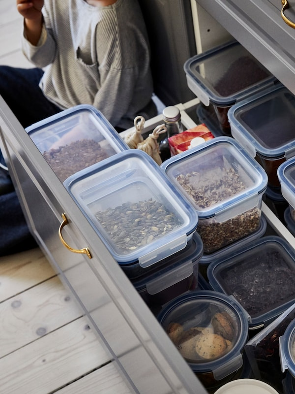 A person sits on the floor next to an open drawer full of different food containers with seeds, nuts and other food inside.