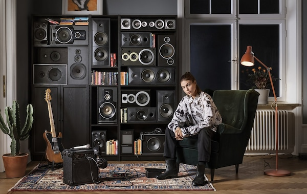 A person sitting in a winged armchair in front of a series of black bookcases filled with speakers.