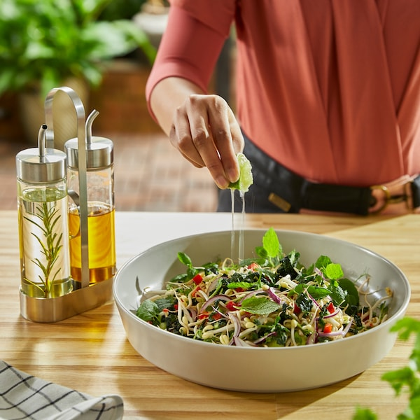 A person squeezes lime juice into a salad in a beige serving plate. A vinegar/oil set in glass/stainless steel stands beside.