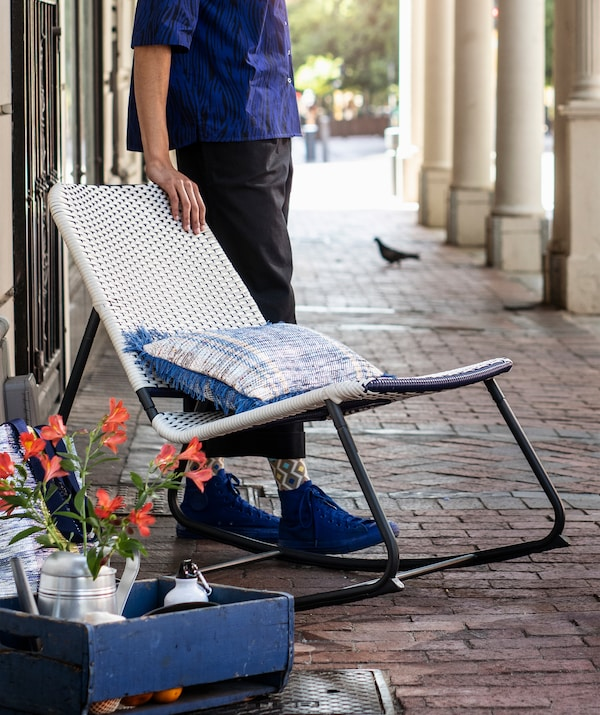 A person standing next to a blue and white rocking chair with metal frame outside.