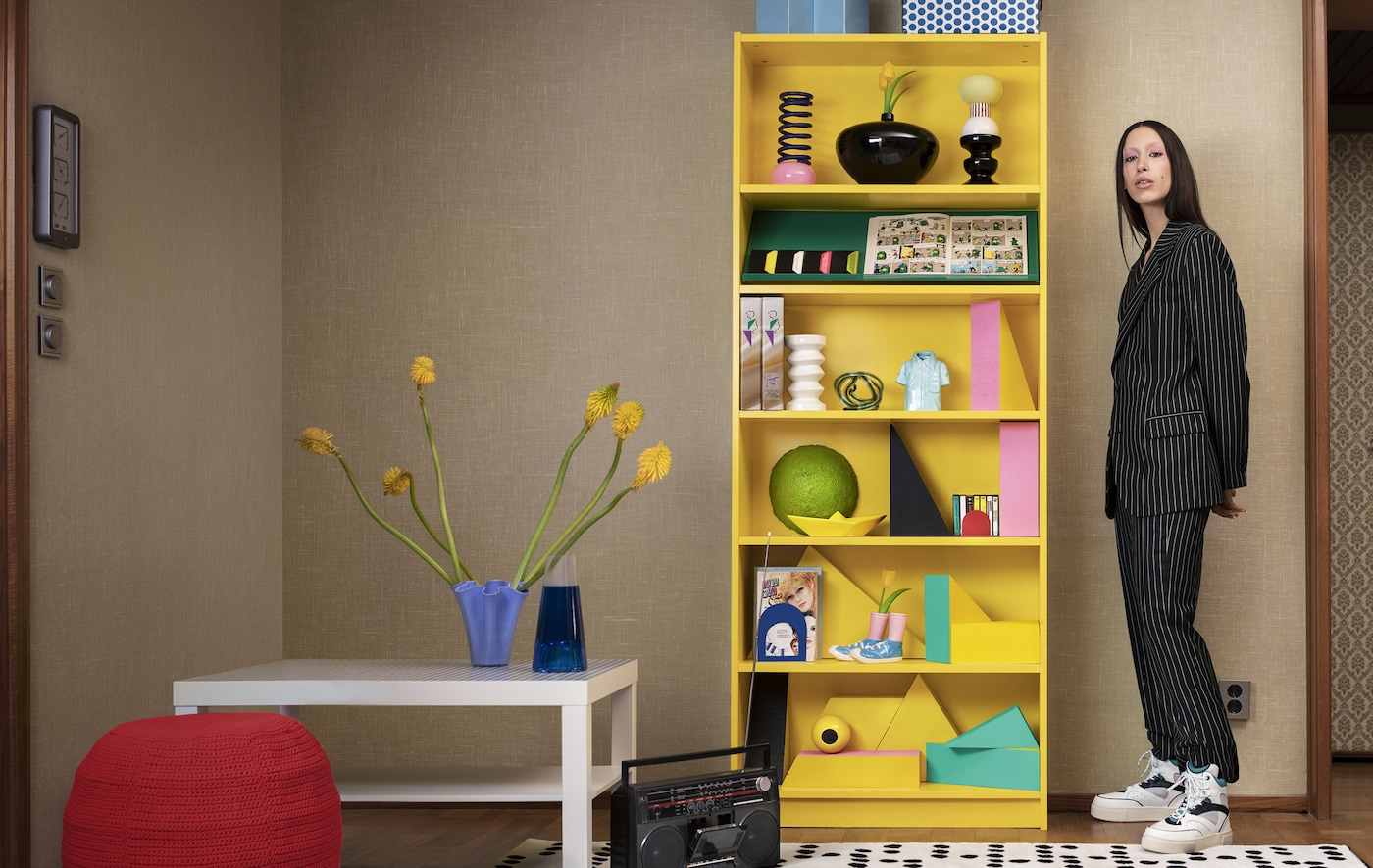 A person standing next to a bright yellow BILLY bookcase with ornaments on the shelves.