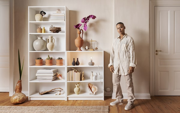 A person standing next to two white bookcases containing books, vases and plants.
