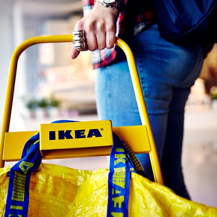 A person using a IKEA shopping trolley.