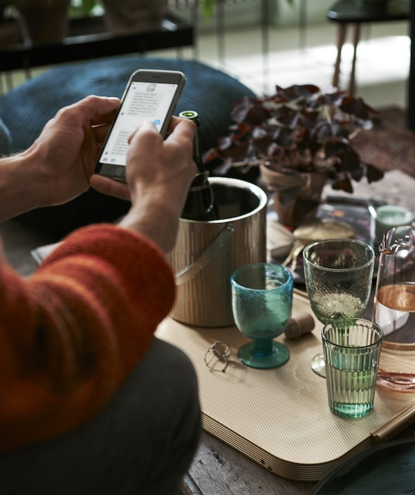 A person using their phone sitting in front of a coffee table with drinks.