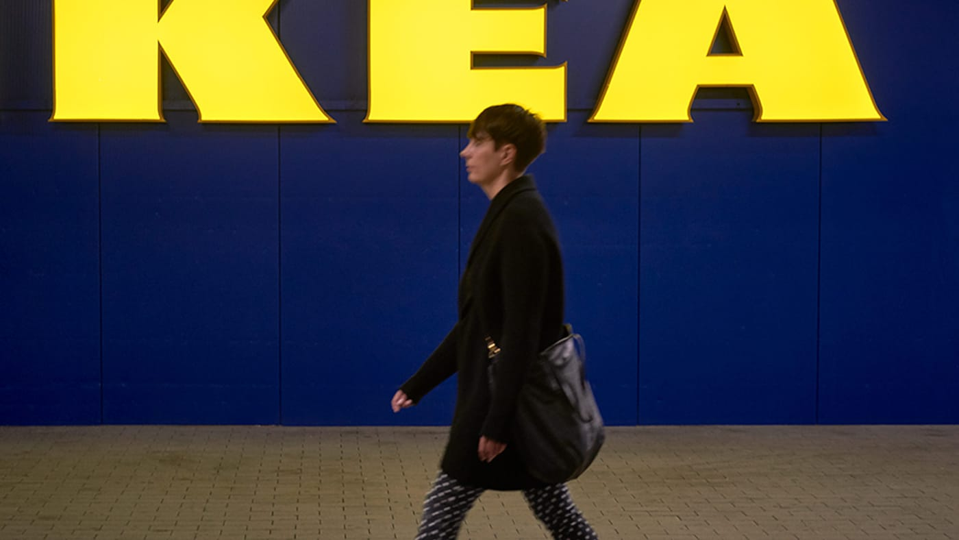 A person walking in front of an IKEA store.