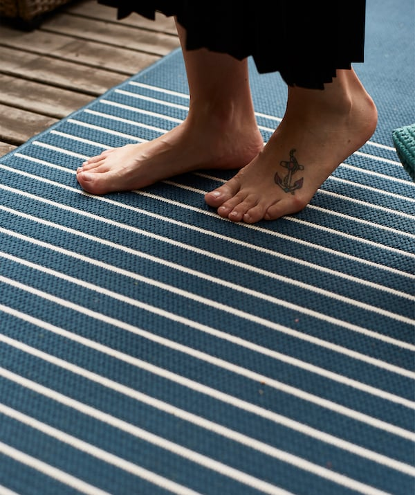 A person walks barefoot on a blue and white striped rug.
