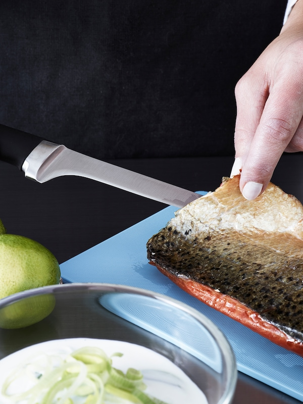 A person wearing a black apron is filleting a piece of fish using a fillet knife with a black handle.