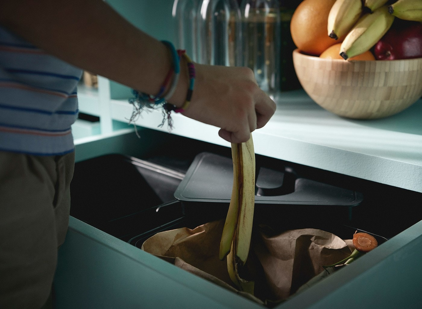 A person wearing bracelets dropping a banana skin in to an IKEA VARIERA recycling bin, in a kitchen drawer.