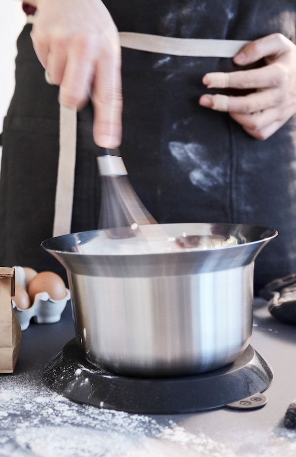 A person whisks with one hand. OMTÄNKSAM mixing bowl has a lid that can be placed underneath to stop it from slipping.