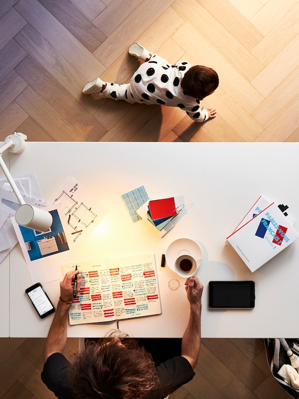 A person working at a home office desk with a cup of coffee and a pen and paper with a baby crawling nearby.