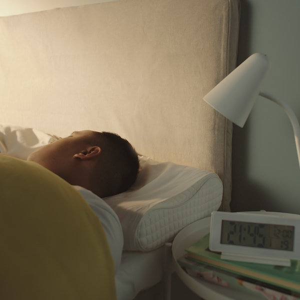 A person's head lying on an ergonomic pillow in bed.