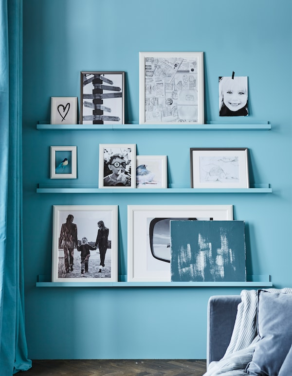 A photo frame wall in a living room made with shelves painted the same color as the wall