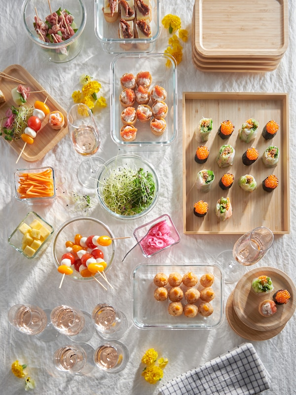 A picnic blanket filled with snacks in various IKEA 365+ food containers in glass.