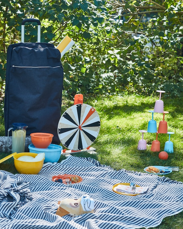 A picnic in the grass with tableware, games, a big blanket and a blue FÖRENKLA XL duffle bag on wheels.